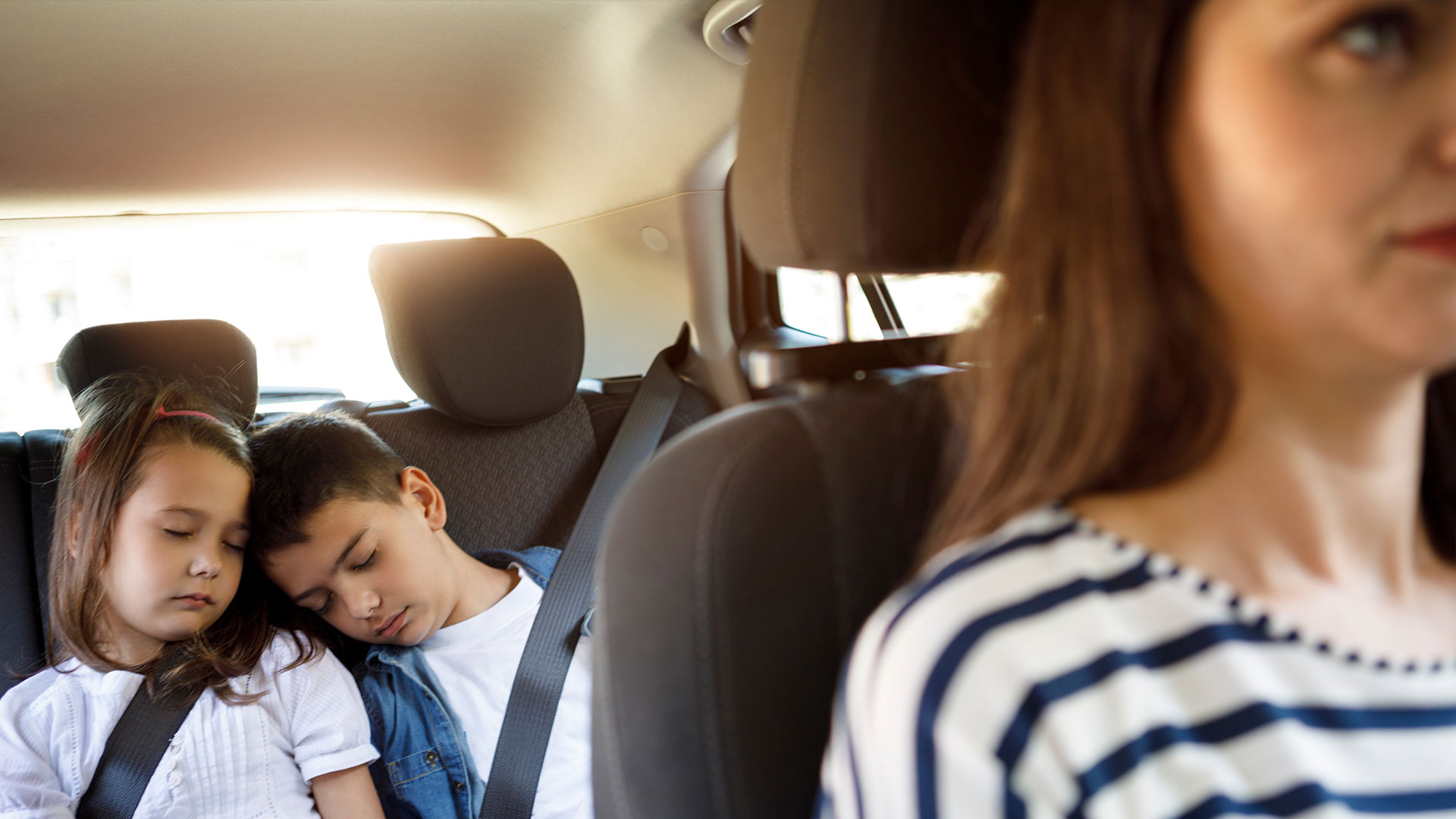 Kids sleeping in the backseat of a car